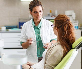 Woman in dental chair talking to dentist