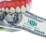 A denture mold holding a $100 bill.