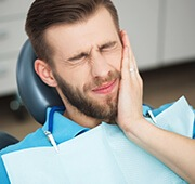 Man holding jaw in pain during emergency dentistry visit