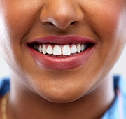 A woman's smile with a small gap between the two front teeth