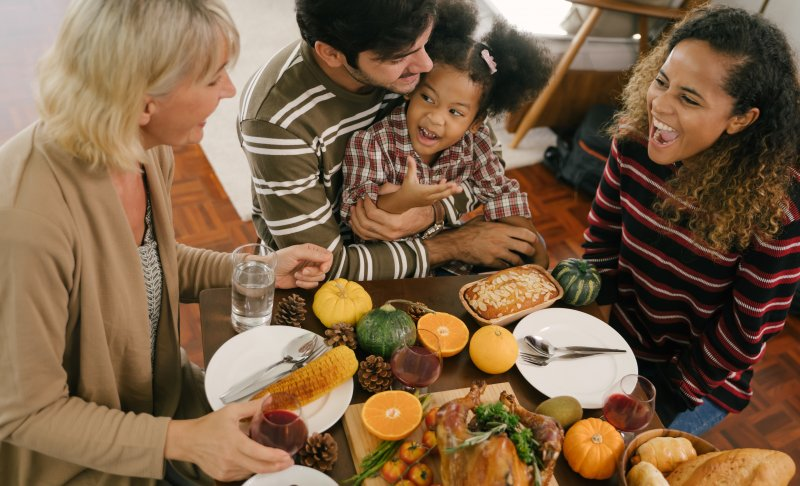 a family seated around a table full of Thanksgiving food