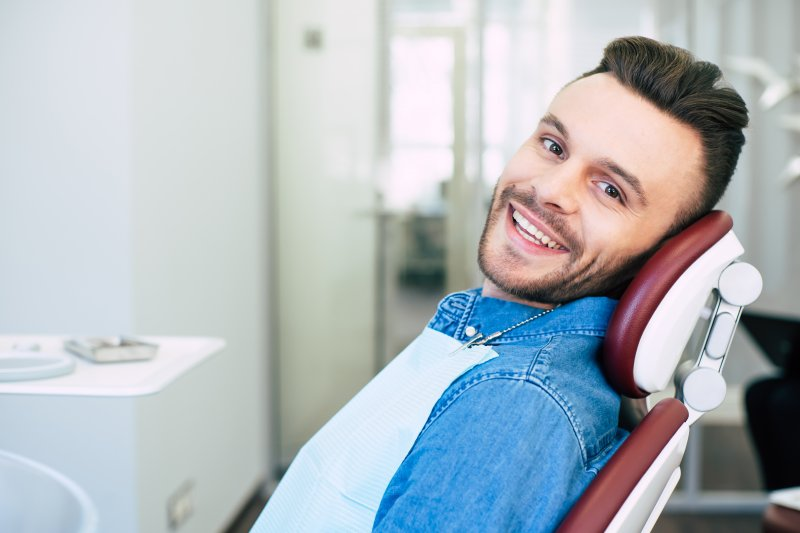 a young man with a beard smiling as he prepares to see his dentist in Salem